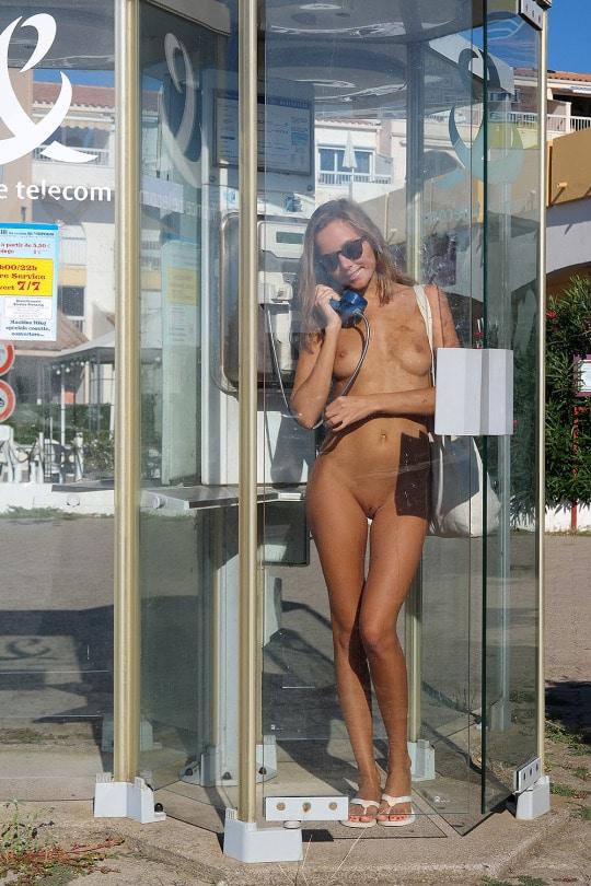 Photo d'une fille sexy et exhib nue dans une cabine téléphonique